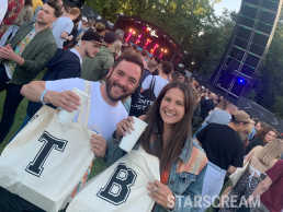 2 people stood infront of a stage at a festival holding tote bags with the letters T and B on them
