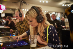 A woman with blonde hair stood in the foregrund listening to music through headphones.