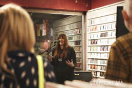 A woman stood talking into a microphone to a small crowd
